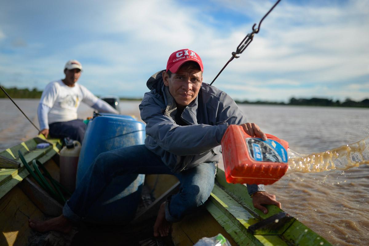 """<h5>Rio Beni</h5><p>Juan Pablo deita borda fora a água que insiste em penetrar no barco que nos transportou ao longo do Beni e que apelidaríamos de Quilombo (""""barafunda"""", naquela zona da Amazónia). Eddy Ocampo (em 2º plano) é o dono da embarcação de 13 metros de comprido e 1,5m de largura e o homem que tornou possível esta travessia de boa parte da floresta amazónica boliviana. Homem versátil e vivido, montou em minutos um acampamento na margem, em plena selva, quando fomos surpreendidos pela noite a quatro horas de distância da próxima localidade.</p>"""