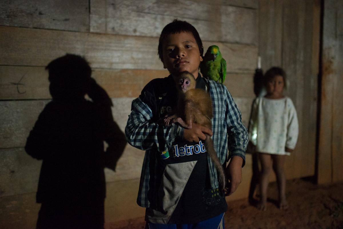 <h5>Puerto Cavinas</h5><p>Como em qualquer lado do mundo, os animais de estimação são adorados pelas crianças. Aqui, um macaco e um papagaio fazem companhia a dois irmãos antes de se irem deitar, após um jantar com yucca frita, uma das especialidades da região.</p>